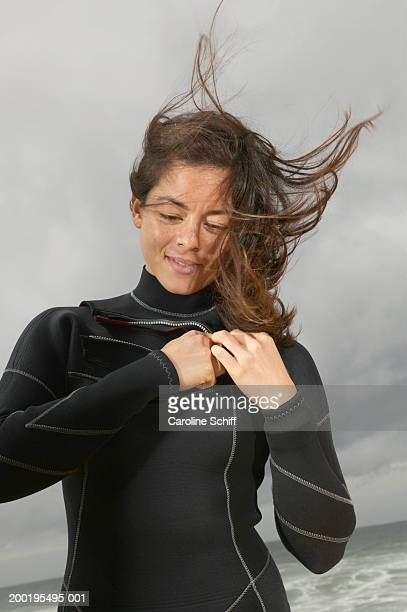 Young woman zipping wetsuit on beach, hair blowing in wind