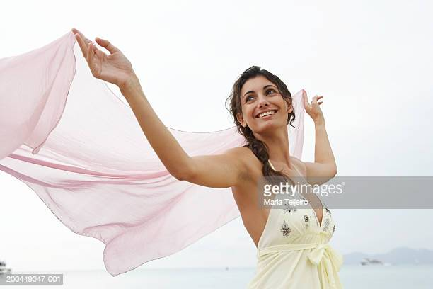 young womanon beach, holding pink stole to catch breeze - shawl stock pictures, royalty-free photos & images