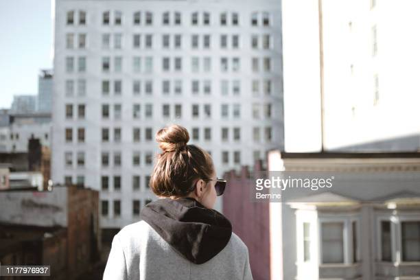 young woman's back in urban setting - hooded top stock pictures, royalty-free photos & images