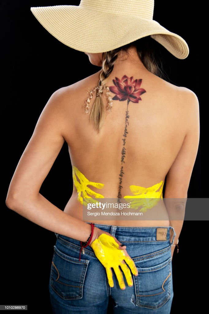 A young woman's back with a lotus flower tattoo and her hands with paint : Stock Photo