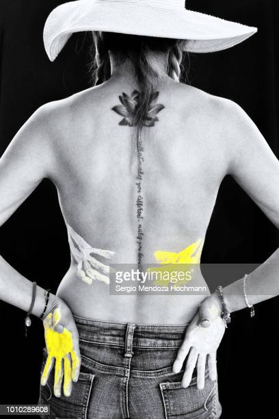 A young woman's back with a lotus flower tattoo and her hands with paint