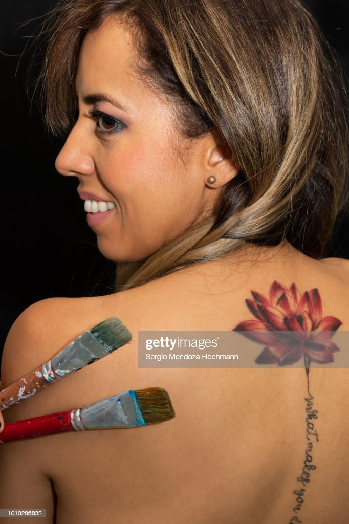 A young woman's back with a lotus flower tattoo holding two paint brushes : Stock Photo