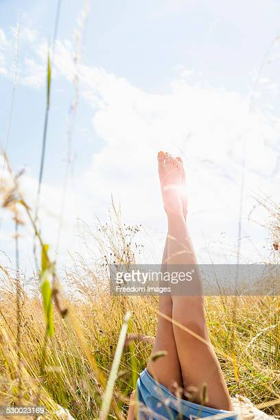 Young womans bare legs in field of long grass