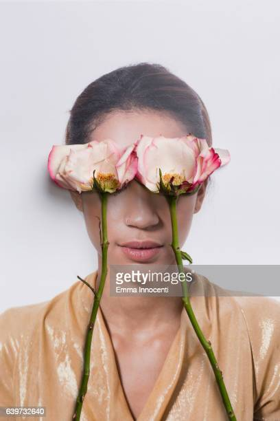 Young woman's eyes covered by roses