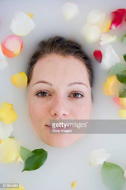 Young woman's face above bath water and surrounded by rose petals