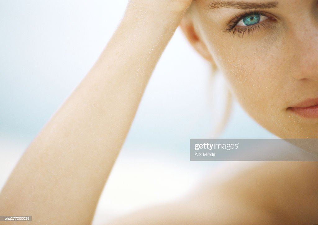 Young woman's face and arm, partial view, looking at camera : Stock Photo