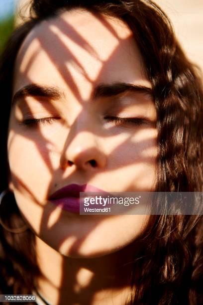 young woman's face in sunlight - donne abbronzate foto e immagini stock