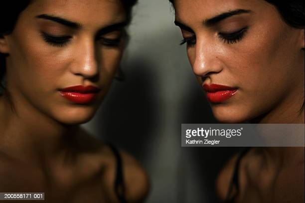 Young woman's face reflecting in mirror, close-up
