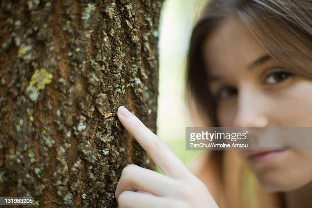 Young woman's finger touching tree trunk, cropped