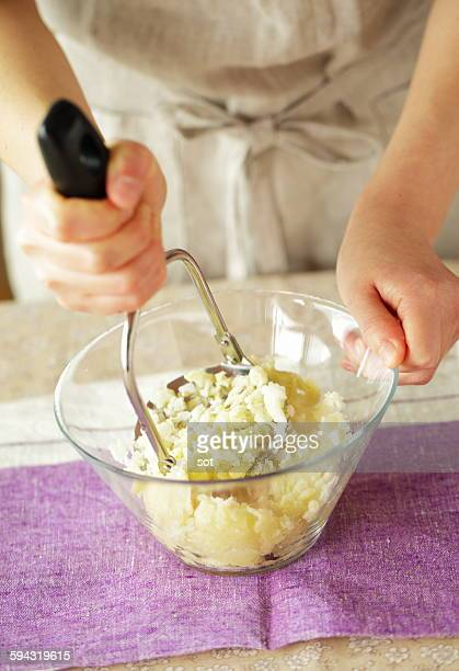Young woman's hand using potato masher