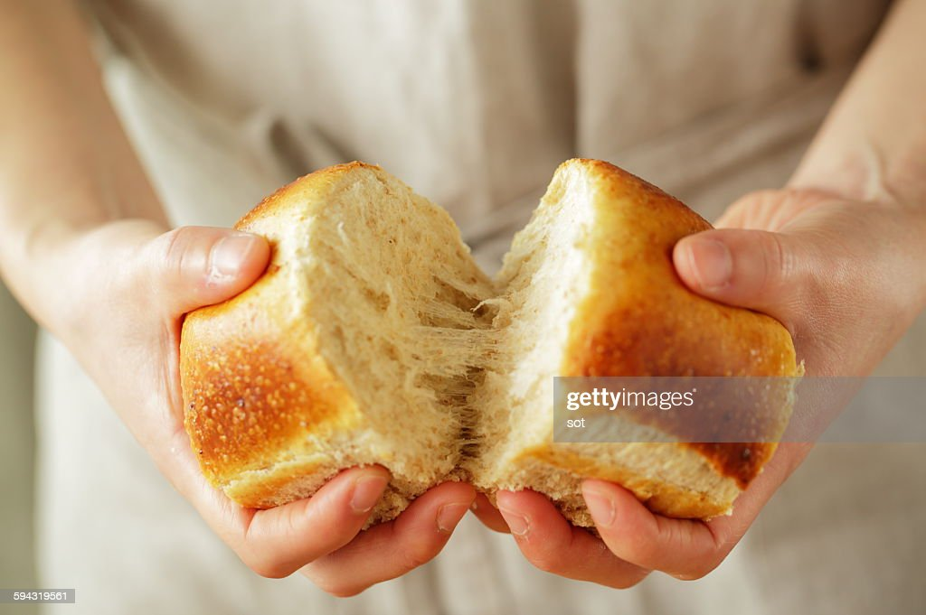 Young woman's hands breaking bread,close up : Stock Photo