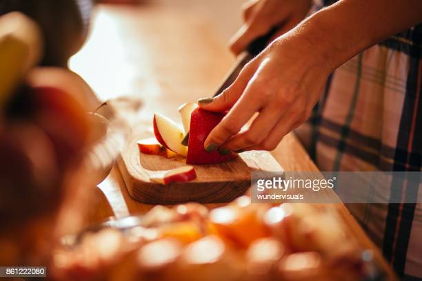 young woman's hands cutting an apple on wooden cut board - apple fruit stock photos and pictures