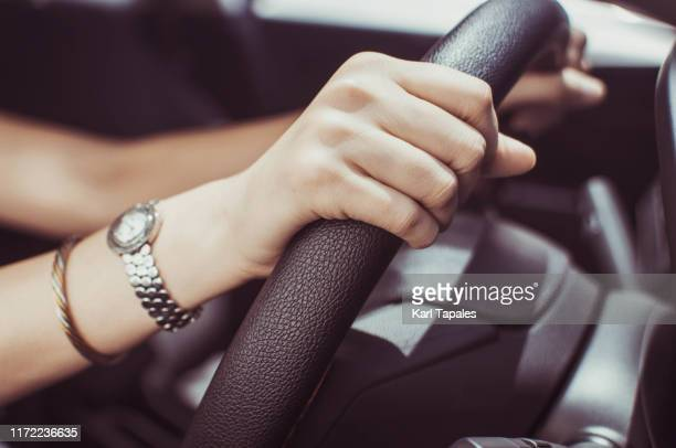 a young woman's hands on a car steering wheel - capital region stock pictures, royalty-free photos & images