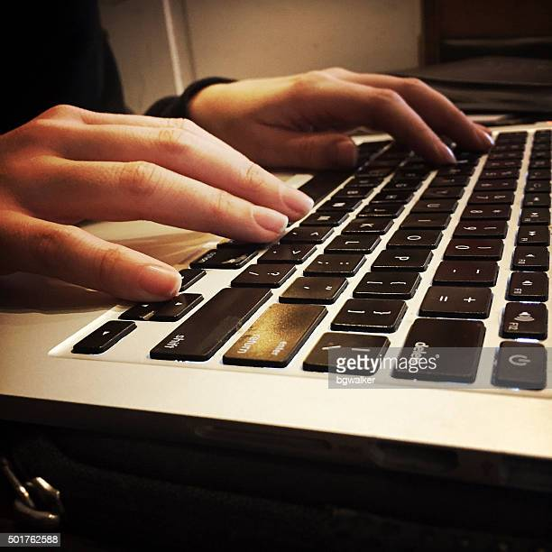 Young Woman's Hands on MacBook Pro Laptop Computer