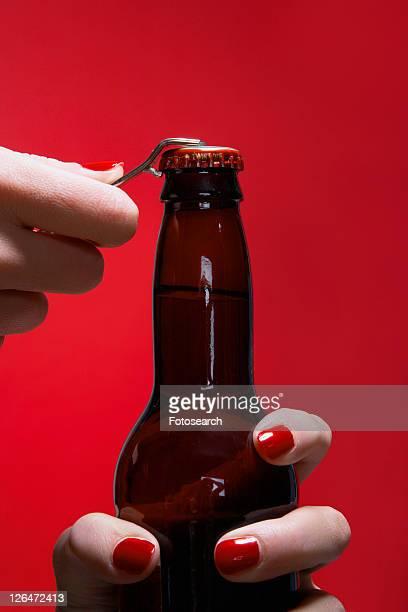 Young woman's hands opening bottle of beer (close-up)