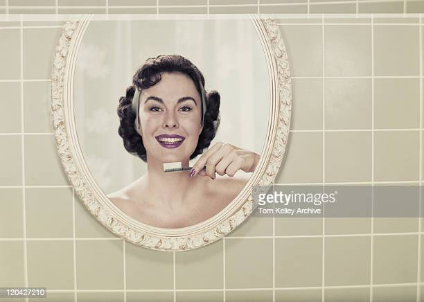 Young woman's reflection in mirror holding toothbrush, smiling, portrait
