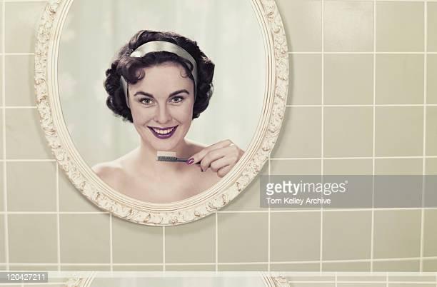 Jeune femme reflet dans le miroir tenant la brosse à dents et souriant,