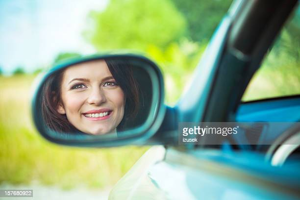Young woman's reflection in side view mirror