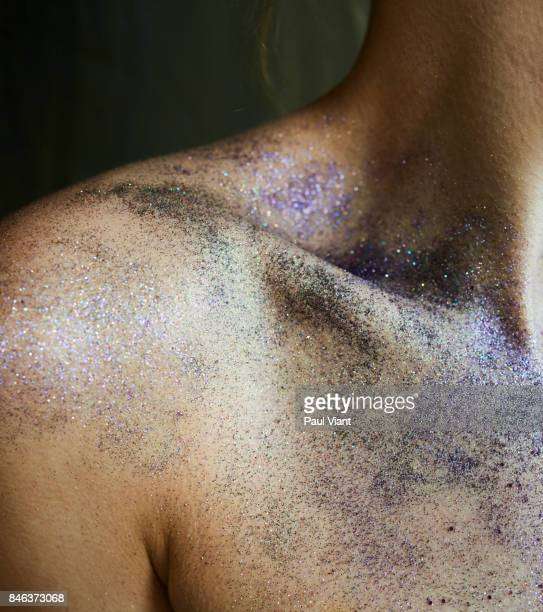 young woman's shoulder with oil and glitter