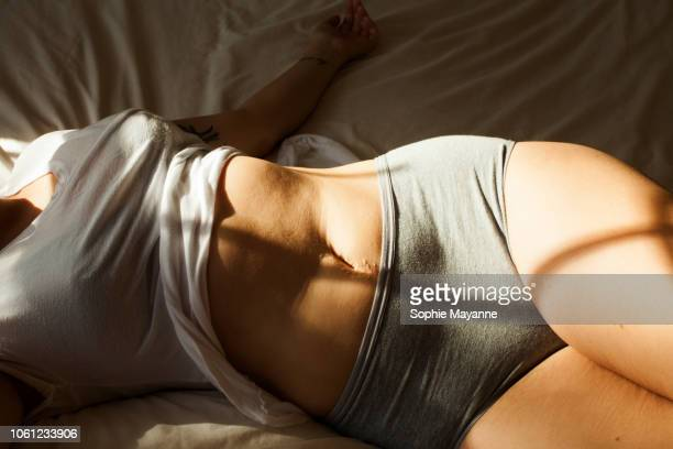 A young woman's torso lying on a bed in sunlight