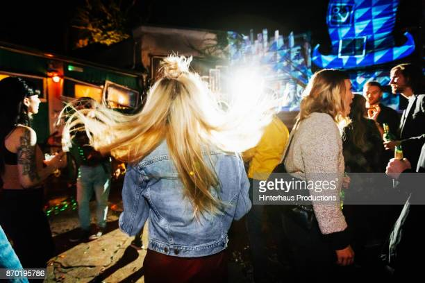 Young Woman'u2019s Hair Flowing As She Dances At Open Air Nightclub