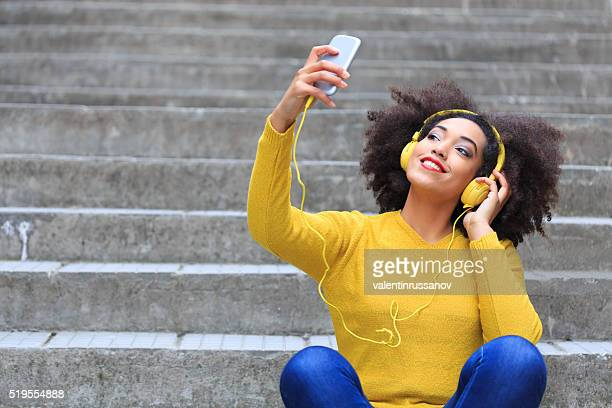 Young womanwith yellow blouse listening music sitting on stairs