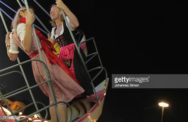 Young womed dressed with traditional Bavarian clothes enjoy riding swingboat during the last day of Oktoberfest beer festival on October 2, 2011 in...