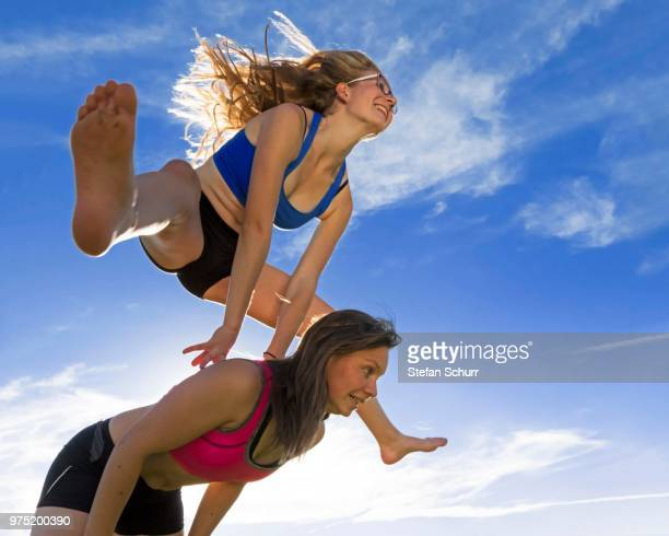Young women, 18 and 20 years, leapfrogging