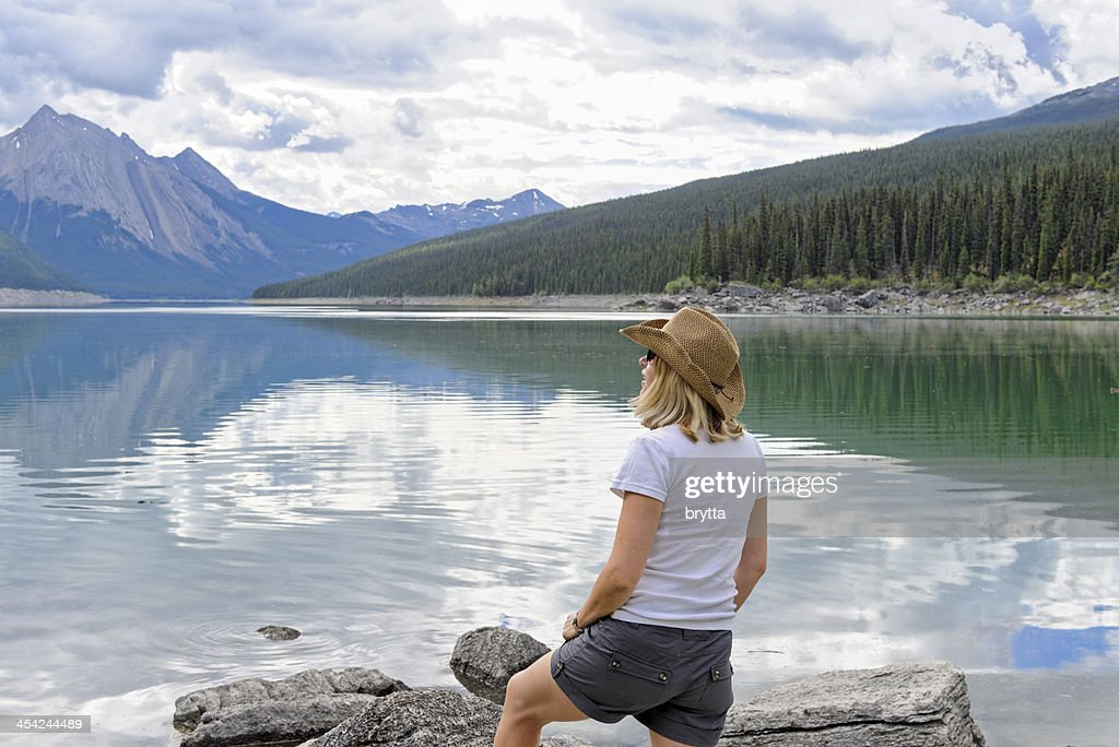 Young women admiring the beautiful lake and mountains : Stock Photo