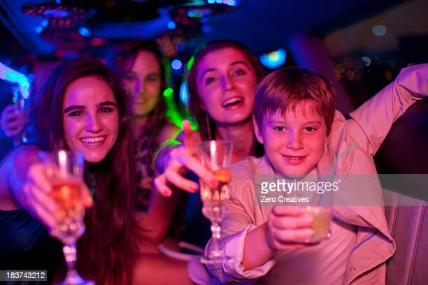 Young women and boy in limousine