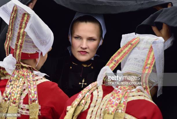 Young women and girls wearing traditional costumes with lace headdresses Festival of Blue Nets Concarneau Brittany France