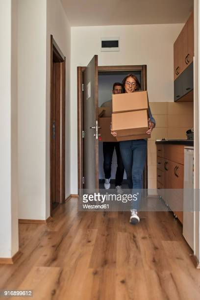 Young women and man carrying cardboard boxes into a room