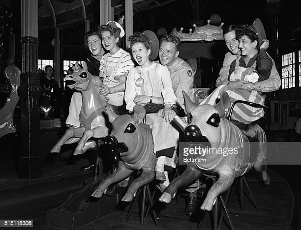 Young women and men enjoying ride on carousel