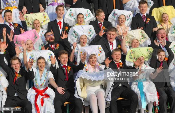 Young women and men taking part in the traditional Zapust festival wear Sorbian-Wendish costumes pose for a picture as they celebrate the driving out...