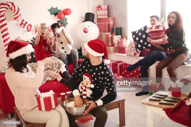 Young women and men throwing popcorn at christmas party