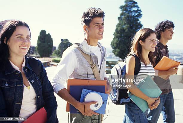 young women and men walking carrying folders, smiling - personal compact disc player stock pictures, royalty-free photos & images