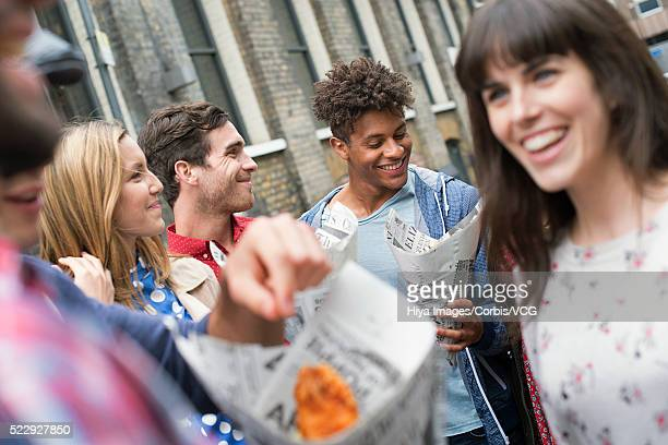 Young women and young men eating fish and chips