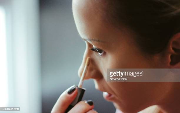 Young women applied concealer under the eyes