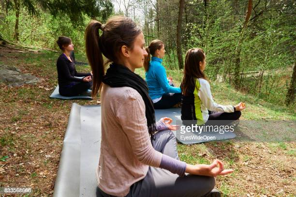 Young women are practicing openair Yoga and Meditation in a forest in the mountains of South Tyrol on April 21 2015 in Lana Italy