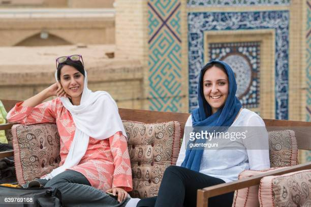 young women are sitting in a rooftop cafe, yazd. iran - iran stockfoto's en -beelden