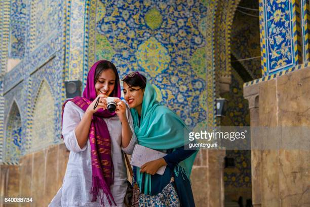 young women are watching images at camera display, isfahan, iran - イラン ストックフォトと画像