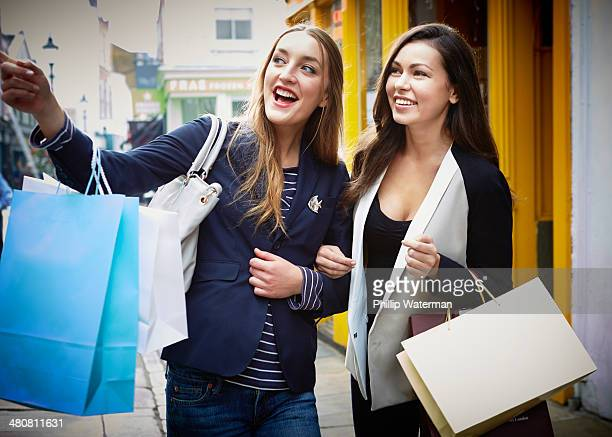 Young women arm in arm, carrying shopping bags down street