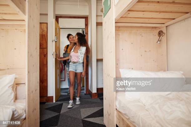 Young women arriving at hostel room with bunk beds