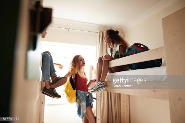 Young women arriving to room with bunk beds, at youth hostel
