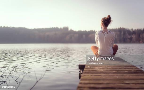 junge frauen an einem hölzernen pier an einem see in österreich - spiritualität stock-fotos und bilder