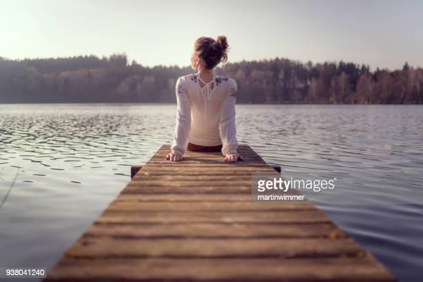 jonge vrouwen op een houten pier op een meer in oostenrijk - meeroever stockfoto's en -beelden