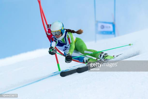 young women at giant slalom against the blue sky - ski stock pictures, royalty-free photos & images