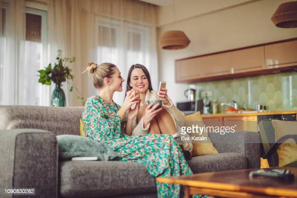 junge frauen zu hause - onlineshopping stock-fotos und bilder