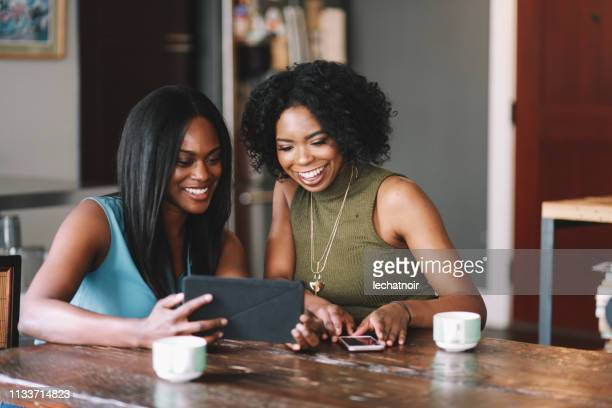 young women at home, watching stuff on tablet together - film in california conference stock pictures, royalty-free photos & images