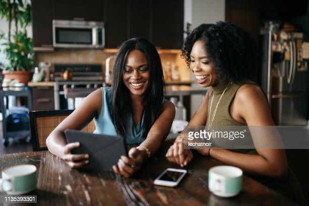 young women at home, watching stuff on tablet together - adult movies stock pictures, royalty-free photos & images